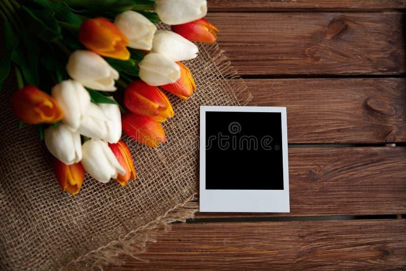 Photo polaroïd avec l'espace noir et le bouquet des tulipes sur le fond en bois brun image libre de droits