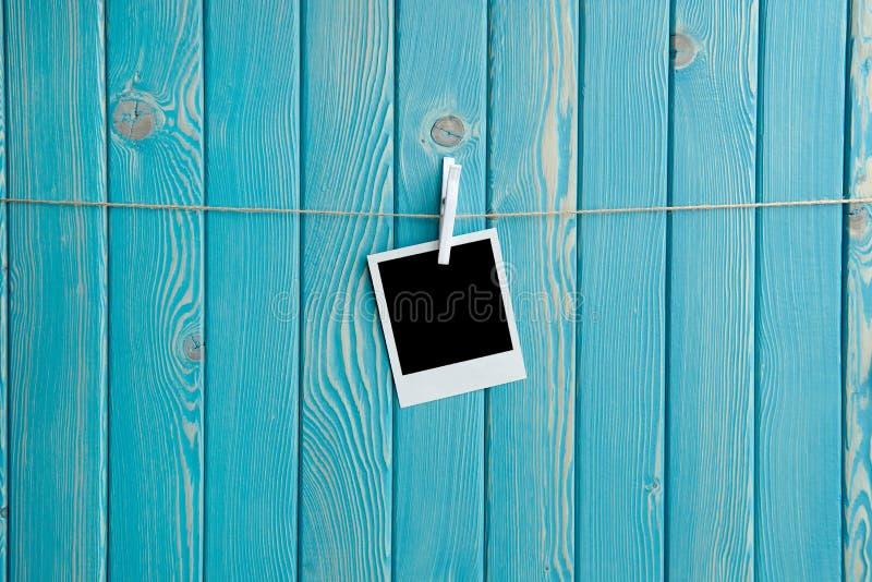 Photo polaroïd avec l'espace noir sur le fond en bois bleu photos libres de droits