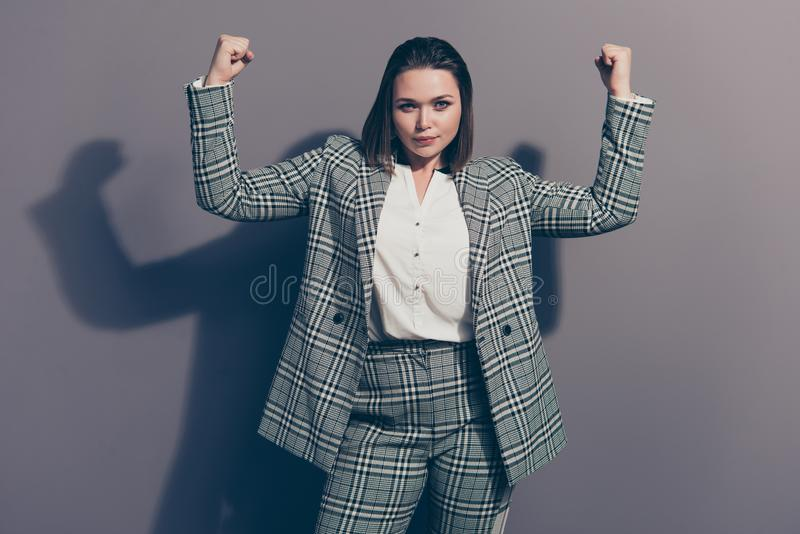 Photo portrait of confident attractive authoritative looking at camera holding demonstrating huge muscles isolated grey. Background royalty free stock photo