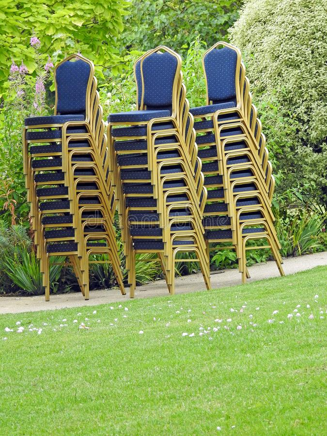 Stack pile seats chairs posh wedding banquet hire. Photo of posh blue satin and gold wedding chairs stacked high after reception stock images