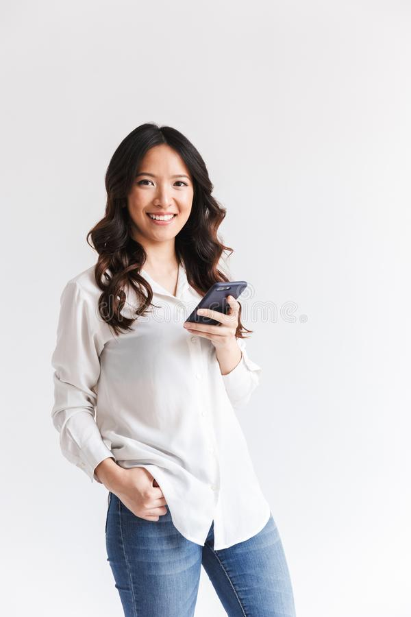 Photo of positive asian woman with long dark hair holding and us stock image