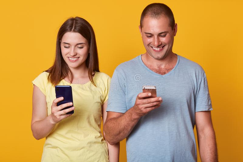 Photo of positive excited man and woman, looking at their smartphones screens with happy expressions, both using mobile phones. Photo of positive excited men and royalty free stock photo
