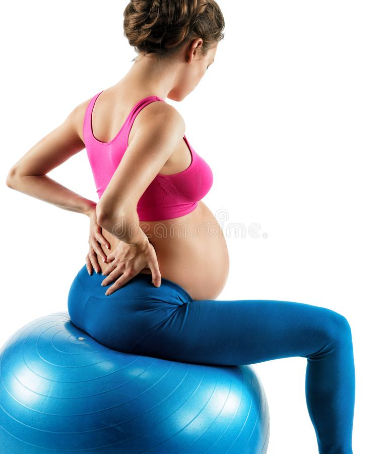 Photo of pregnant woman holding her back in pain isolated on white background. Lower back pain. Photo of pregnant woman holding her back in pain isolated on stock photos