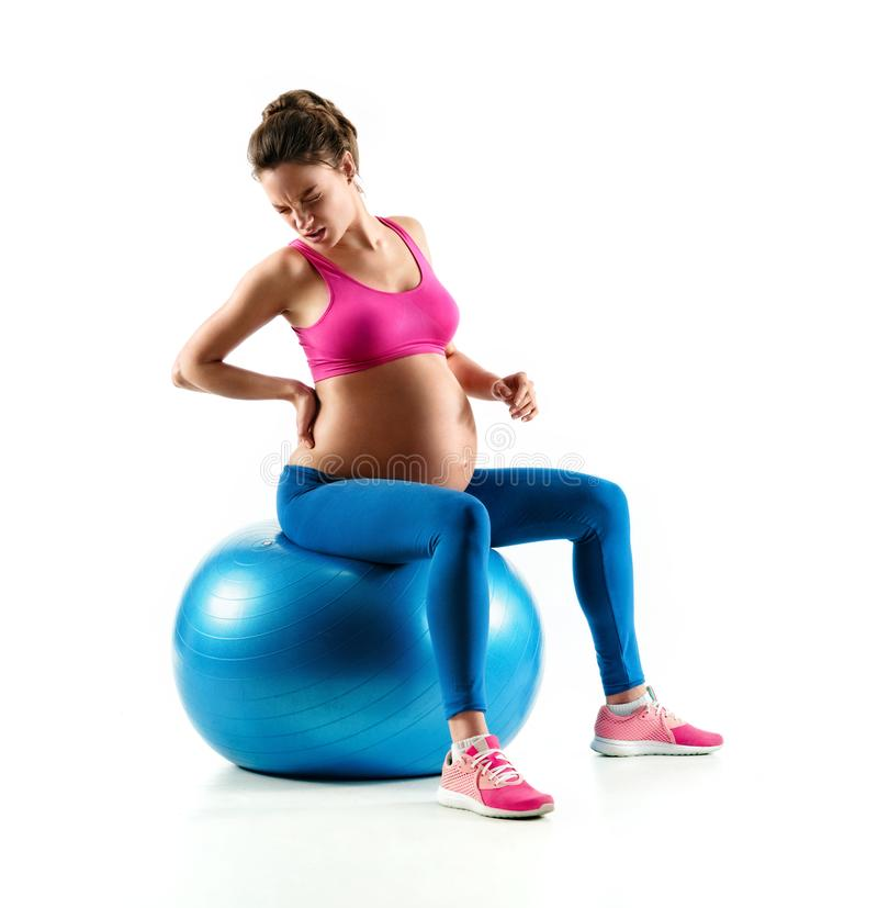 Photo of pregnant woman holding her back in pain isolated on white background. Lower back pain. Photo of pregnant woman holding her back in pain isolated on royalty free stock photos