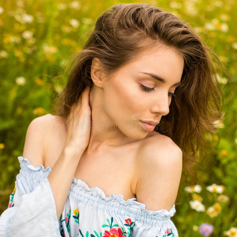 Photo of pretty brunette woman in chamomile field royalty free stock photography