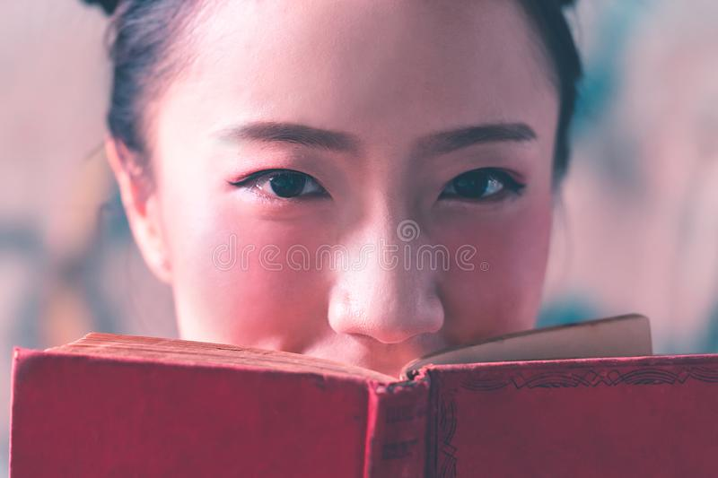 Photo of pretty lady covering face with red book royalty free stock photo