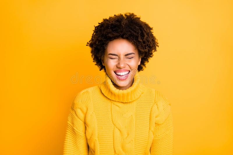 Photo of pretty dark skin lady laughing out loud with closed eyes wear warm knitted jumper isolated yellow color royalty free stock image