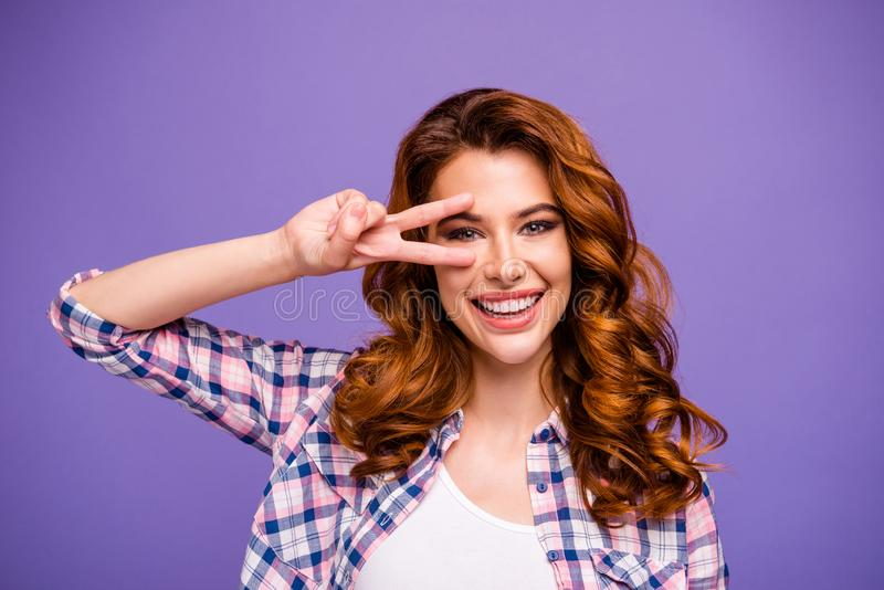 Photo of pretty foxy lady raising arms showing v-sign symbol near eye wear plaid casual shirt isolated purple color royalty free stock image