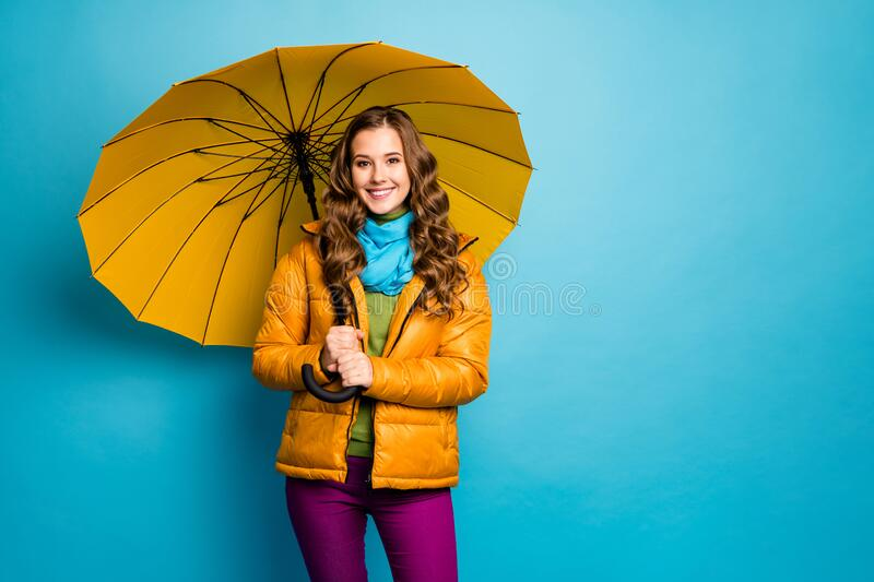 Photo of pretty lady hold bright umbrella enjoy sunny day walk street good mood wear yellow overcoat blue scarf violet. Photo of pretty lady hold bright umbrella stock images