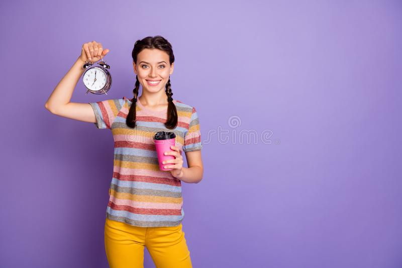Photo of pretty lady holding cup hot beverage drink metal alarm clock fresh early morning good help for lazy people wear stock image