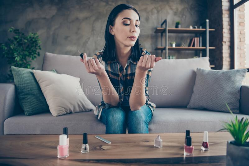Photo of pretty lady made correction finger nails applying final polish coat blowing helping dry wear casual clothes royalty free stock photos