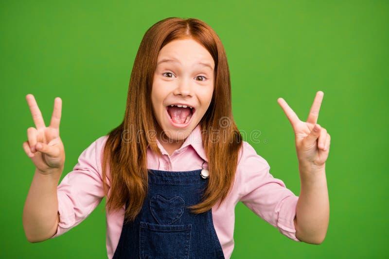 Photo of pretty little foxy schoolchild near chalkboard showing v-sign symbol glad to see classmates after summer. Photo of pretty little foxy schoolchild near stock photo