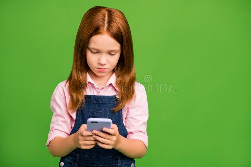 Photo of pretty little schoolchild holding telephone hands searching homework additional information wear denim overall. Photo of pretty little schoolchild stock images