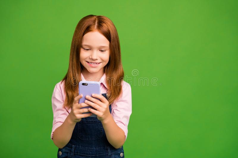 Photo of pretty little schoolchild holding telephone hands texting with classmates friends reading sms wear denim. Photo of pretty little schoolchild holding royalty free stock image