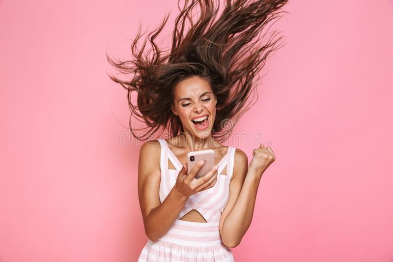 Photo of pretty woman 20s wearing dress smiling and holding smartphone with hair shaking, isolated over pink background royalty free stock photography