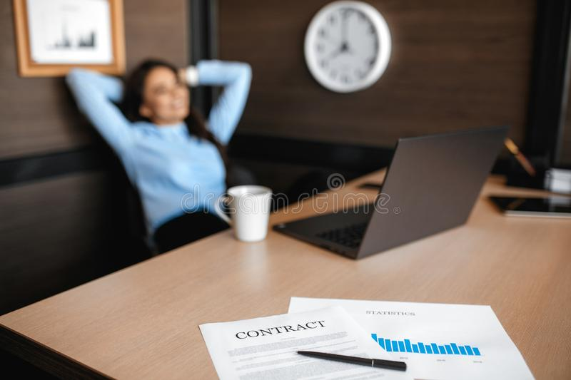 Photo of pretty young manager woman relaxing after working with laptop in modern office. Celebrating success. royalty free stock photo