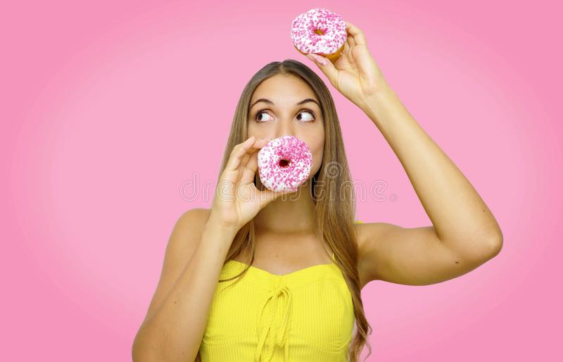 Photo of pretty young woman standing isolated over pink background holding donuts in front of mouth and on her head looks to the royalty free stock photo
