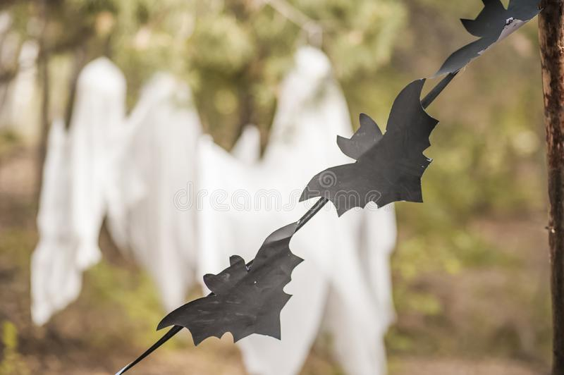 A photo project for Halloween in nature. A garland of black drawn bats against the backdrop of three white ghosts in a forest of g. Auze. Place and background royalty free stock image