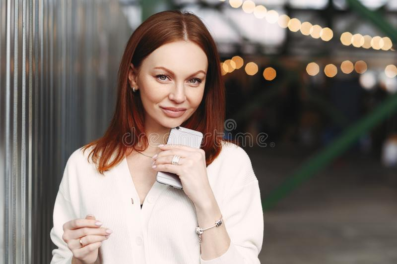 Photo of prosperous female business worker has break after work, sends text messages, holds cell phone in hand, dressed in white stock photography