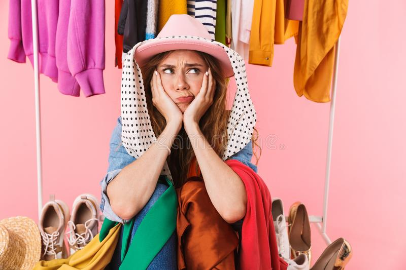 Photo of puzzled young woman wearing hat sitting near bunch of clothes royalty free stock photos