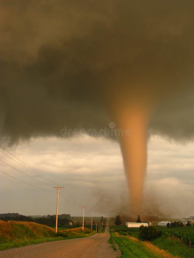 Photo réelle d'une tornade illuminée par le coucher de soleil atterrissant en Iowa, manquant étroitement une ferme photo stock