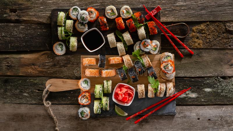 Photo réglée de nourriture de sushi Rolls a servi du plat brun en bois et d'ardoise Vue haute et supérieure de fin des sushi 16 d image libre de droits