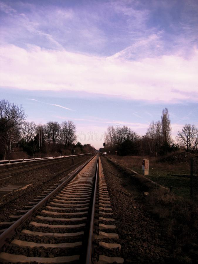 Photo with the railroad in an unusual purple color shades, merging on the horizon with the background of the ominous clouds of th. E sky, as the source for stock photo