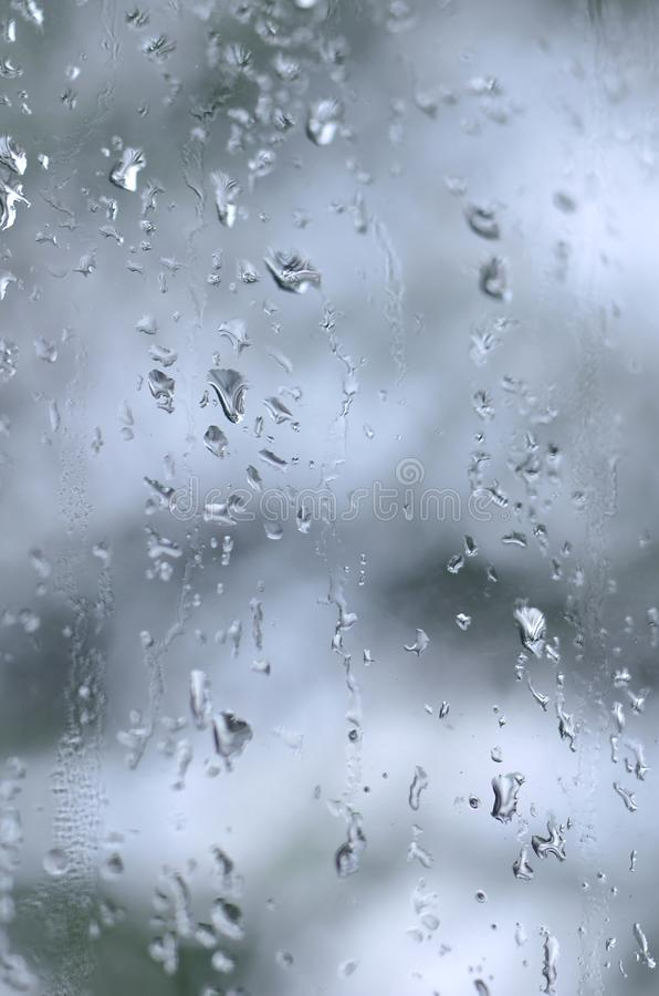 A photo of rain drops on the window glass with a blurred view of the blossoming green trees. Abstract image showing cloudy and ra. Iny weather conditions stock photos