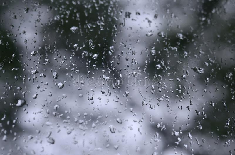 A photo of rain drops on the window glass with a blurred view of the blossoming green trees. Abstract image showing cloudy and ra. Iny weather conditions royalty free stock photography