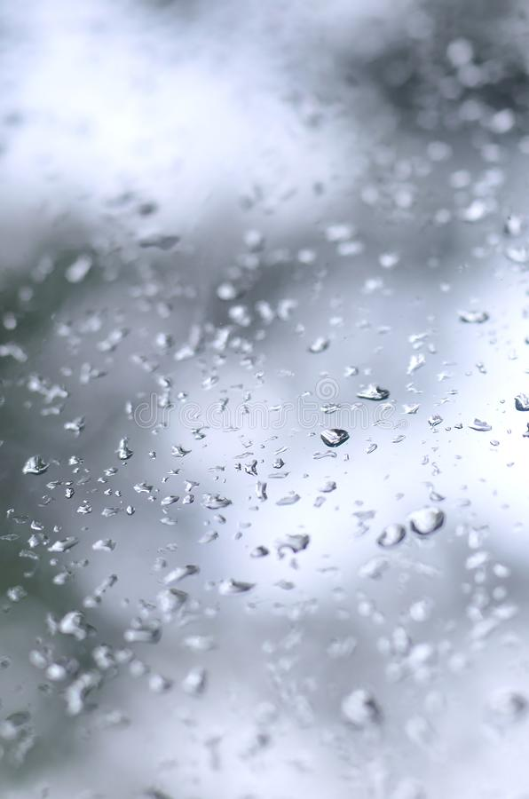 A photo of rain drops on the window glass with a blurred view of the blossoming green trees. Abstract image showing cloudy and ra. Iny weather conditions royalty free stock images