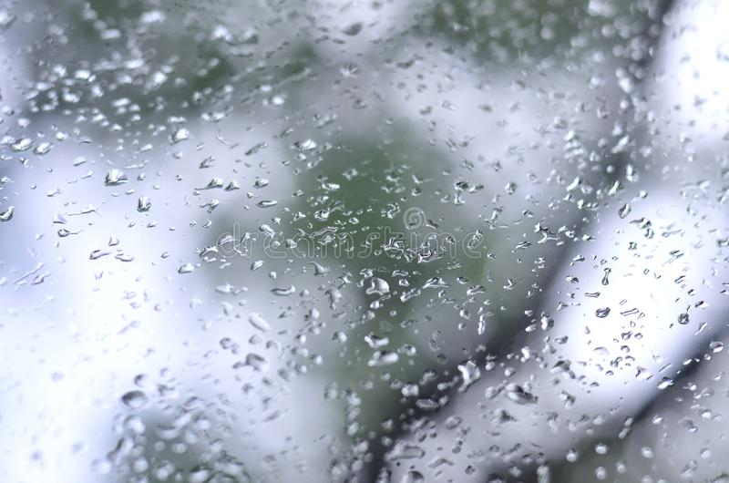 A photo of rain drops on the window glass with a blurred view of the blossoming green trees. Abstract image showing cloudy and ra. Iny weather conditions royalty free stock photo