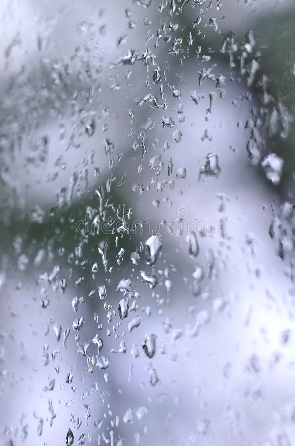 A photo of rain drops on the window glass with a blurred view of the blossoming green trees. Abstract image showing cloudy and ra. Iny weather conditions royalty free stock photos