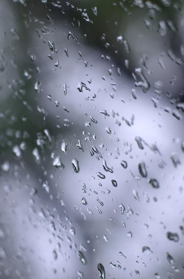 A photo of rain drops on the window glass with a blurred view of the blossoming green trees. Abstract image showing cloudy and ra. Iny weather conditions stock photography