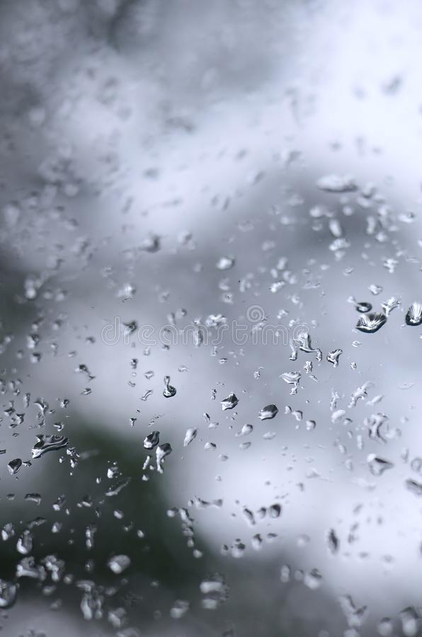 A photo of rain drops on the window glass with a blurred view of the blossoming green trees. Abstract image showing cloudy and ra. Iny weather conditions stock images