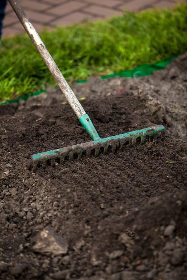 Photo of rake on garden bed stock photo