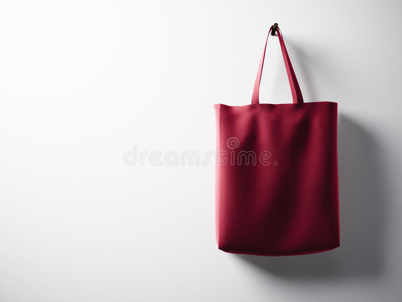 Photo red cotton textile bag hanging right side. Empty white wall background. Highly detailed texture, space for advertising. Hori stock photos