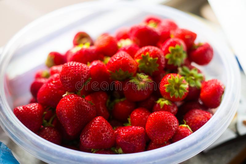 Red fresh and tasty strawberries in a transparent bowl royalty free stock photography