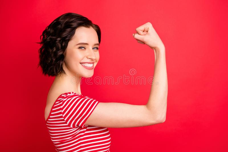 Photo of rejoicing wavy curly woman after having done two pushups while isolated with red background. Photo of rejoicing wavy, curly woman after having done two stock image