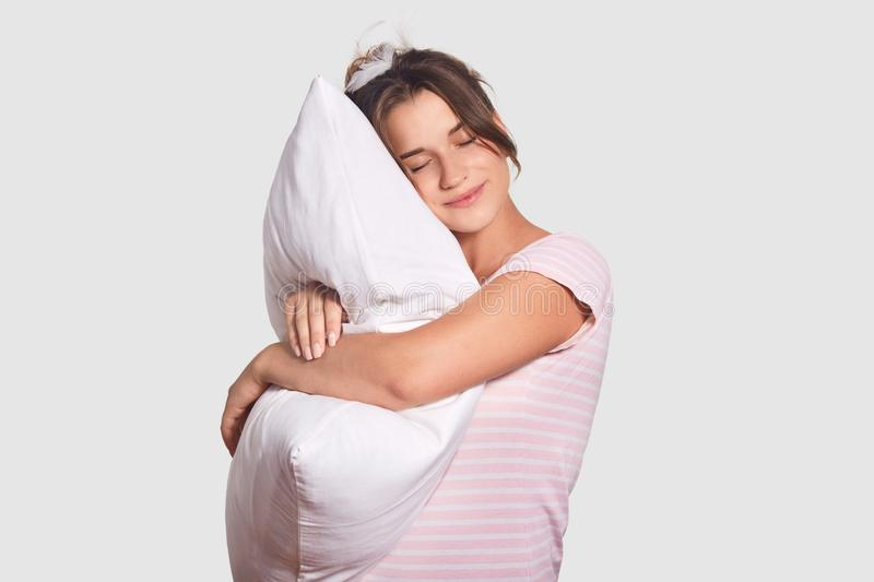 Photo of relaxed young female has sweet dreams, embraces soft pillow, wears nightclothes and has feathers on head, has good sleep. Indoor, poses against white stock images