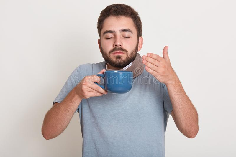 Photo of relaxing young man holding blue mug, smelling and drinking tea or coffee. Handsome guy enjoying drinking tea or coffee royalty free stock photos