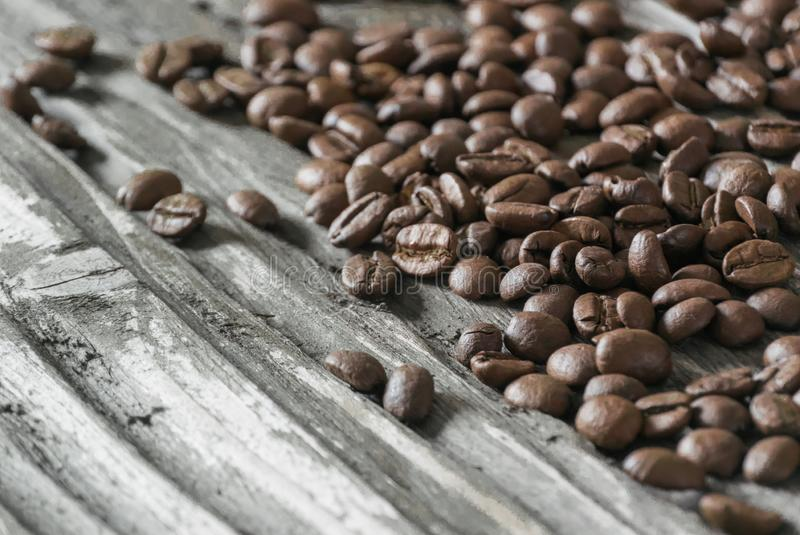 Roasted, fragrant coffee beans lie on the old wooden textured table in the bright rays of the morning sun. royalty free stock photo