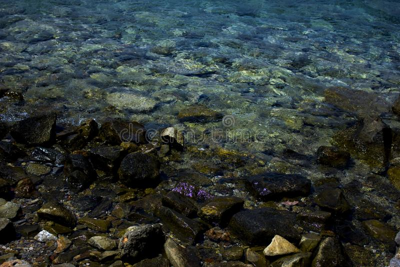 Photo of rocks in water. Photo of rocks in ocean water. Marine landscape photography in blue colors royalty free stock image