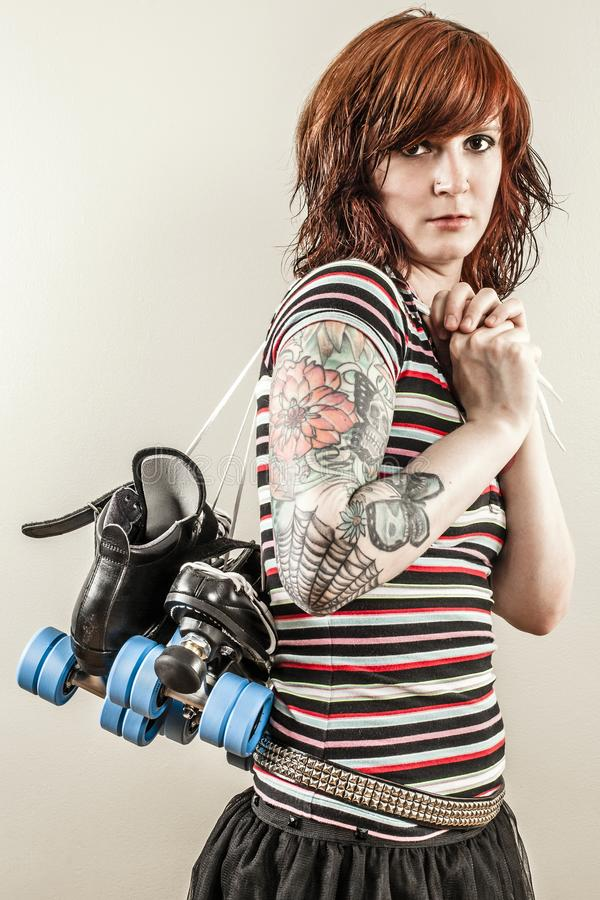 Beautiful roller derby woman holding skates royalty free stock image
