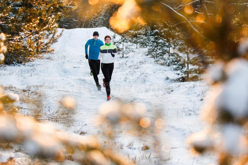 Photo of running sports woman and man in winter park stock photos