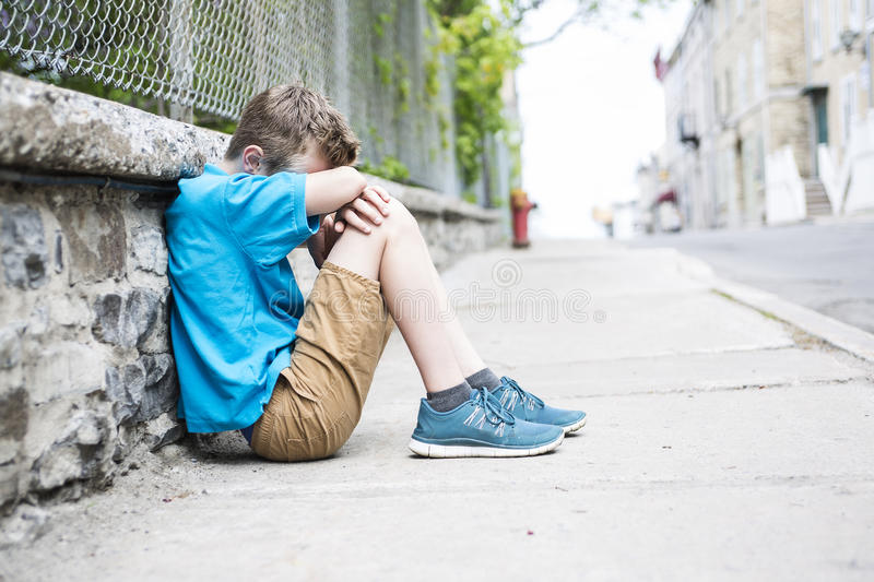 Photo of Sad and Stressed Kid sit by the Wall outdoor royalty free stock photography
