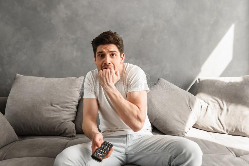 Photo of scared man biting his fist in fear while sitting on couch in gray apartment, and holding remote control for tv in hand. Photo of scared man biting his royalty free stock photos