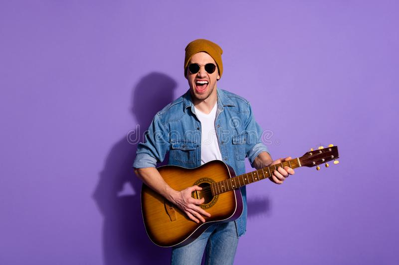 Photo of screaming stubble cheerful handsome attractive musician casting shadow on wall behind isolated over purple. Photo of screaming stubble cheerful handsome royalty free stock photo