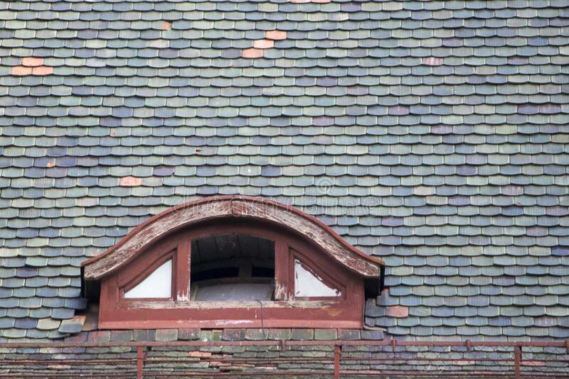 Photo of a semi round garret opening on a shingled roof. stock photos