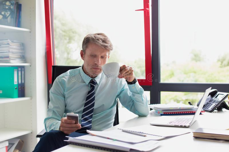 Senior business man drinking a coffee and checking smart phone  whilst sitting in his small real life office. Photo of Senior business man drinking a coffee and royalty free stock images