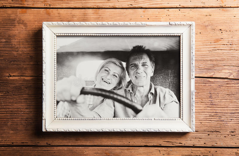 Photo of seniors in picture frame laid on wooden background. Black-and-white photo of seniors driving a car in white picture frame. Studio shot on brown wooden royalty free stock image